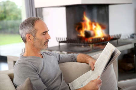 at resting: Mature man relaxing by fireplace with newspaper Stock Photo