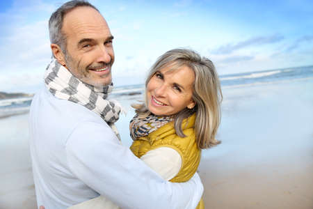couple winter: Portrait of loving senior couple at the beach Stock Photo