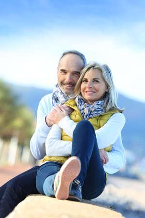 man woman hugging: Senior couple sitting by the beach