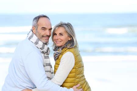 Senior paar zittend op het strand