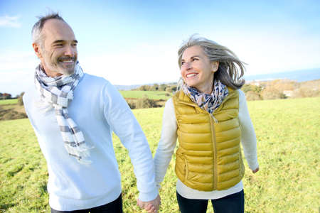 jubilados: Alegre matrimonios de edad corriendo en el campo
