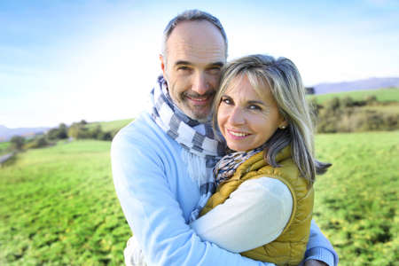 winter couple: Senior couple embracing in countryside