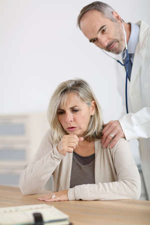 hurting: Senior woman being examined by doctor for cough