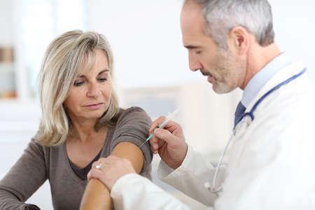 vacunaci�n: Doctor que inyecta la vacuna a la mujer mayor