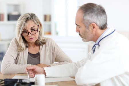 artritis: Doctor que da la medicina a la mujer senior para el dolor de la artritis