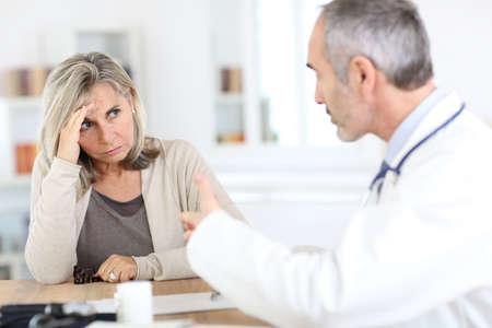 Doctor giving medicine to senior woman for arthritis pain photo