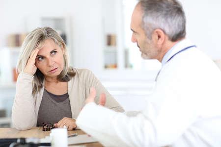 medicalcare: Doctor giving medicine to senior woman for arthritis pain