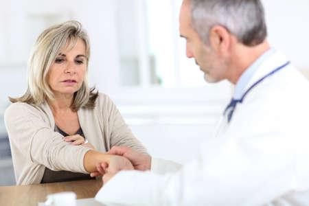 Hogere vrouw met pols pijn consulting arts