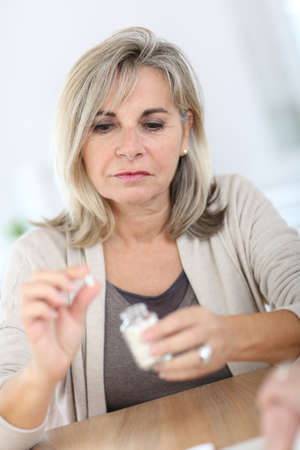 Senior woman taking pills for arthritis pain photo
