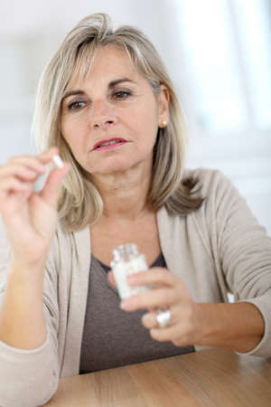 arthritis pain: Senior woman taking pills for arthritis pain Stock Photo
