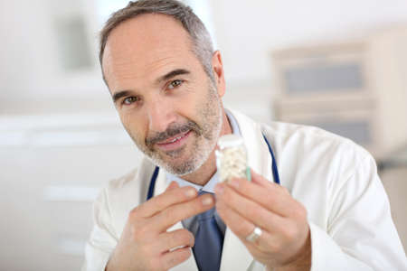 Portrait of doctor holding box of pills photo