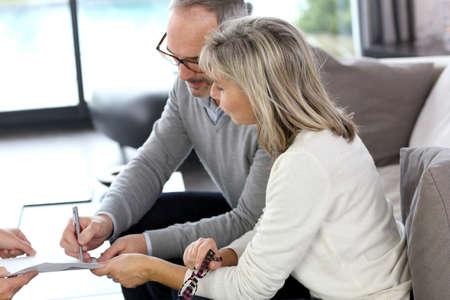 firmando: Matrimonios de edad de firmar el contrato de bienes raíces Foto de archivo