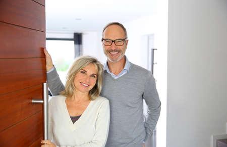 vítejte: Senior pár přivítat lidé vstoupit domů Reklamní fotografie