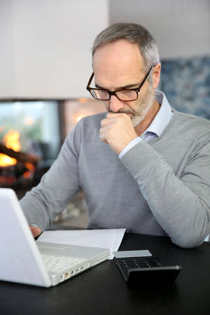 Mature man working from home with laptop computer photo