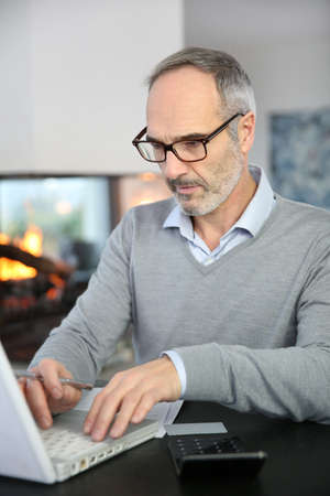 working from home: Mature man working from home with laptop computer