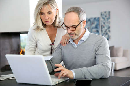 Senior couple at home using internet on laptop computer Stock Photo - 24141181