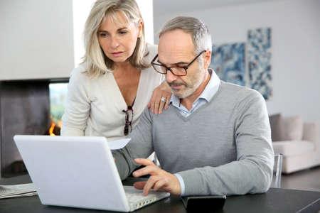 Ältere Paare, die zu Hause mit Internet auf Laptop-Computer