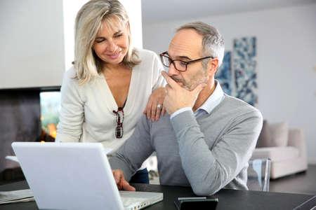 senior ordinateur: Couple de personnes �g�es � domicile en utilisant Internet sur ordinateur portable
