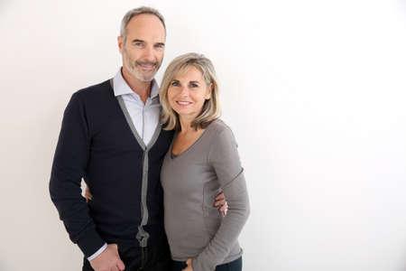 白い背景上に立っている陽気な年配のカップル