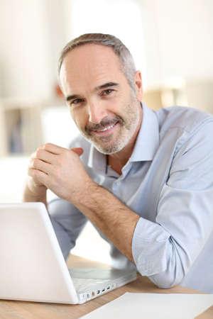 Senior businessman working on laptop computer photo