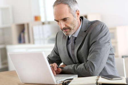 50 years old man: Senior businessman working on laptop computer Stock Photo