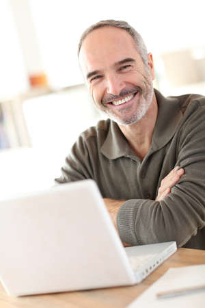 mature men: Smiling mature man sitting in front of laptop Stock Photo