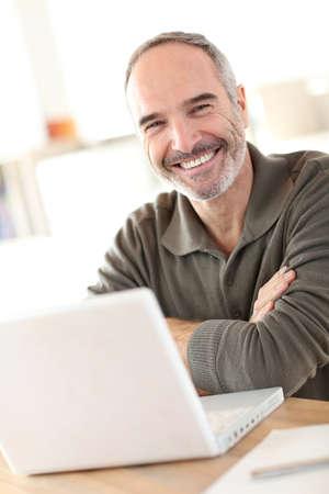 hombres maduros: Sonriente hombre maduro sentado delante de la computadora portátil