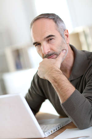 50 years old man: Senior man working from home with laptop computer