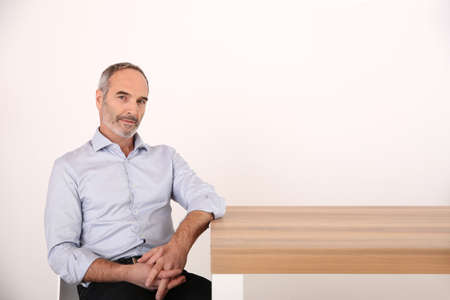 Attractive senior businessman sitting at table photo