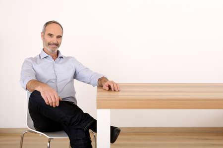 テーブルに座って魅力的なシニア ・ ビジネスマン