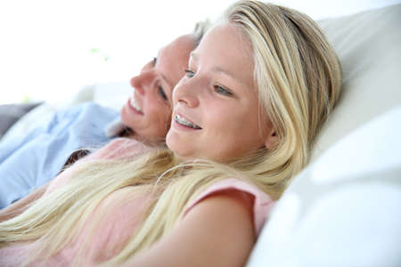 blonde mom: Mother and daughter relaxing in sofa, looking away
