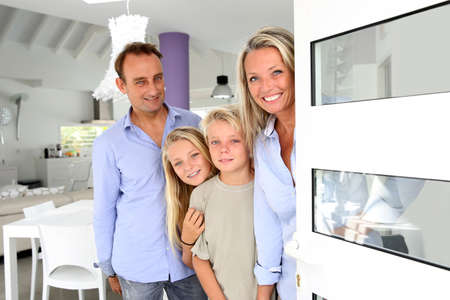 abriendo puerta: La familia feliz bienvenida a la gente en su casa
