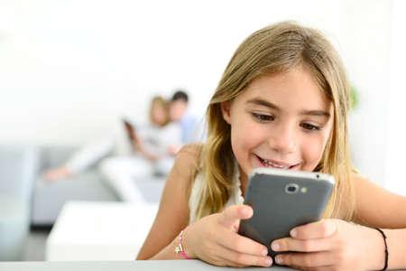 Bambina sorridente che gioca con lo smartphone