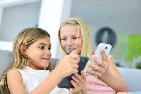 Giovani ragazze che giocano insieme con lo smartphone