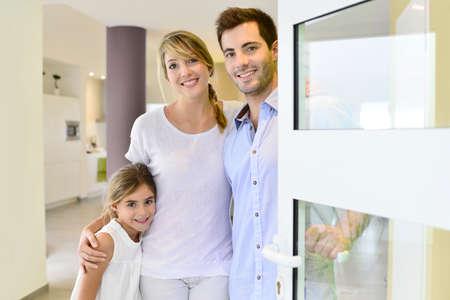 abriendo puerta: Familia que se coloca en la puerta delantera de invitar a las personas en