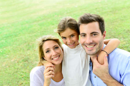 Portrait of happy family standing in park photo