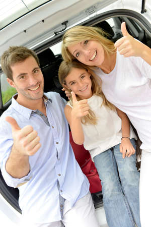 Cheerful family in car trunk showing thumbs up photo