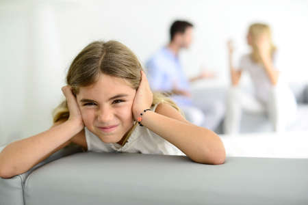 Little girl tired of earing her parents yelling at each other photo