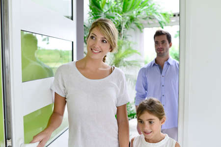 entrance: Family of three walking in new home Stock Photo