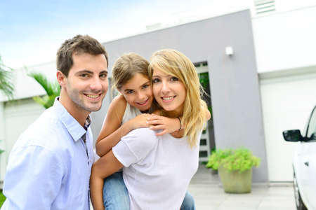 Parents with kid standing in front of new home photo