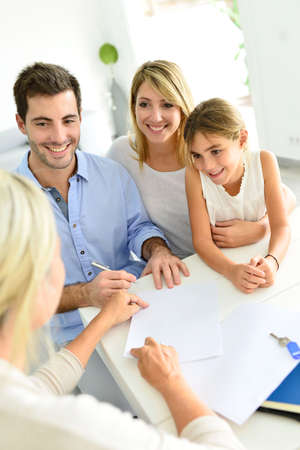 Family signing contract with home seller photo