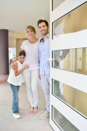 Familie die zich bij de voordeur om mensen uit te nodigen in Stockfoto