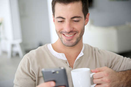Man at home connected on smartphone photo