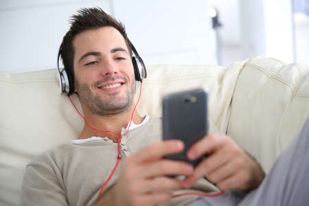 Young man relaxing in sofa with headphones on photo