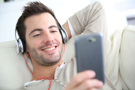 Young man relaxing in sofa with headphones on Stock Photo - 24564434
