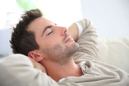 Man taking a nap in sofa Stock Photo