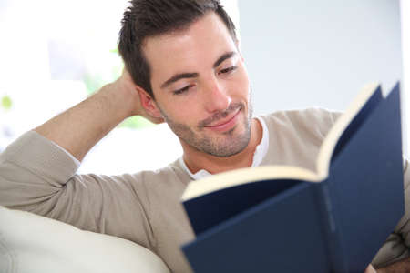 Man in sofa reading book photo