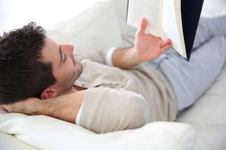 Man in sofa reading book Stock Photo - 24564448