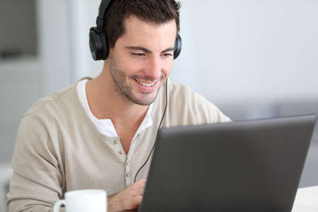 distant work: Man in front of laptop computer with headset