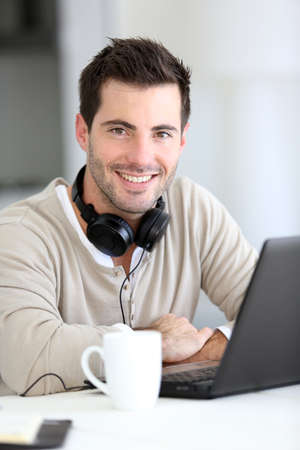 Man in front of laptop computer with headset photo